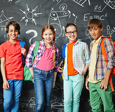 Children with backpacks in front of chalkboard