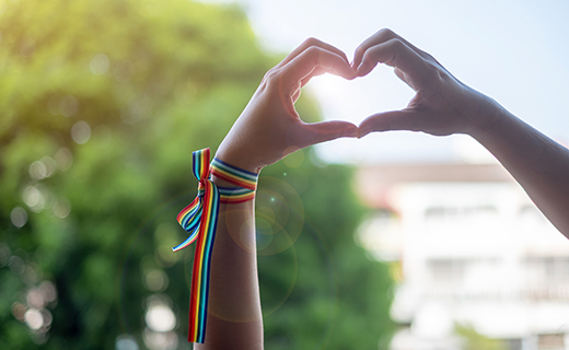 Hands making a heart shape with a rainbow ribbon.