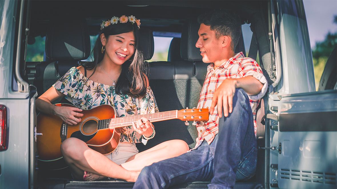 Girl and boy playing a guitar in the back of a car.