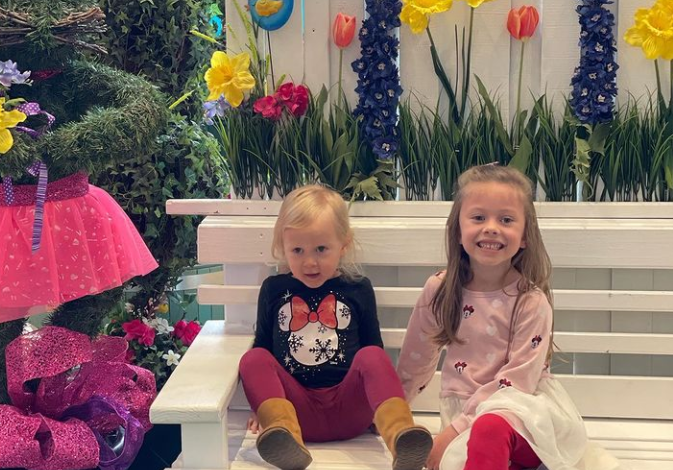 Two little girls sitting on bench with spring decor.