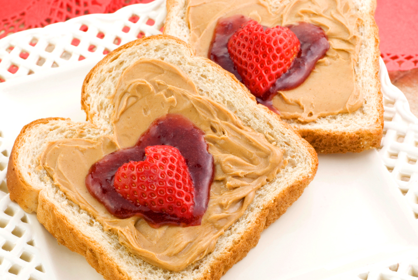 Bread slices with Peanut Butter, Jelly and heart shaped strawberries.