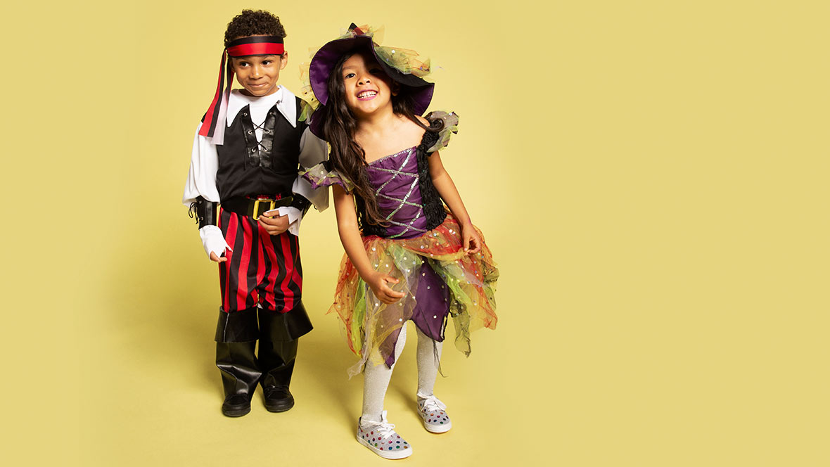 Two Children dressed in a pirate and witch costume with a yellow back drop.