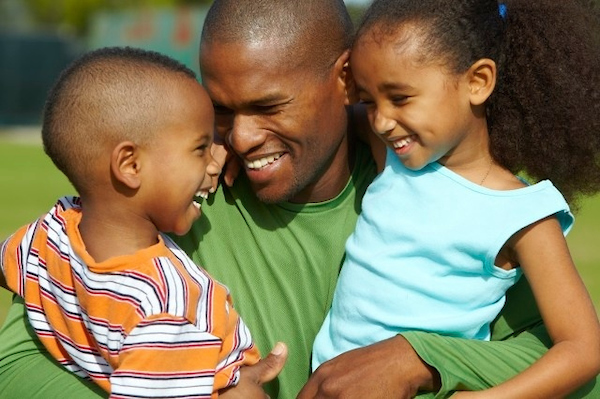 father hugging son and daughter laughing.