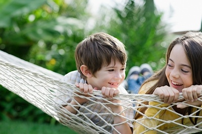two kids on a hammock laughing