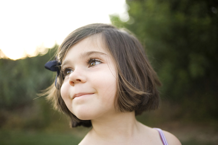 little girl standing looking side profile and smiling.