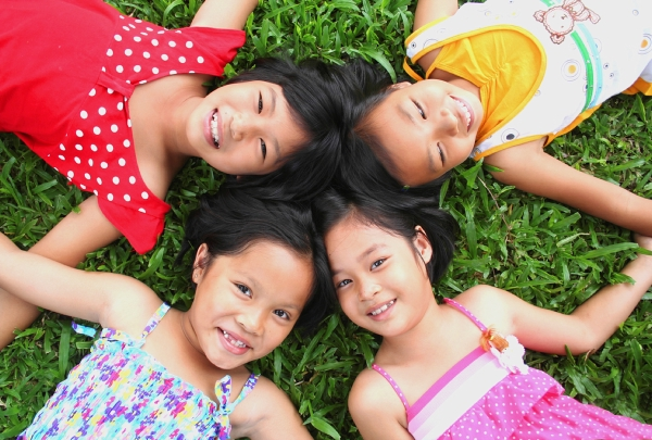 4 little girls laying in the grass looking up and smiling.