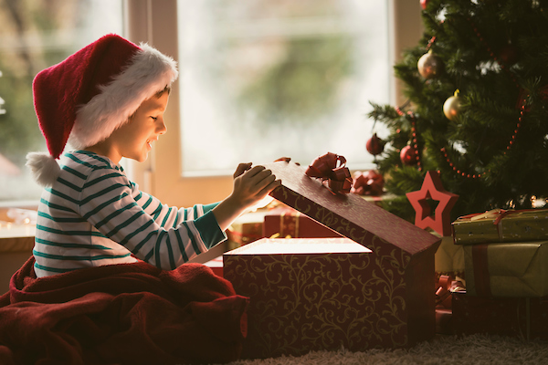 little boy opening a Christmas present smiling under the tree.