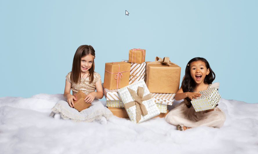 Two little girls on fake snow with pile of gifts