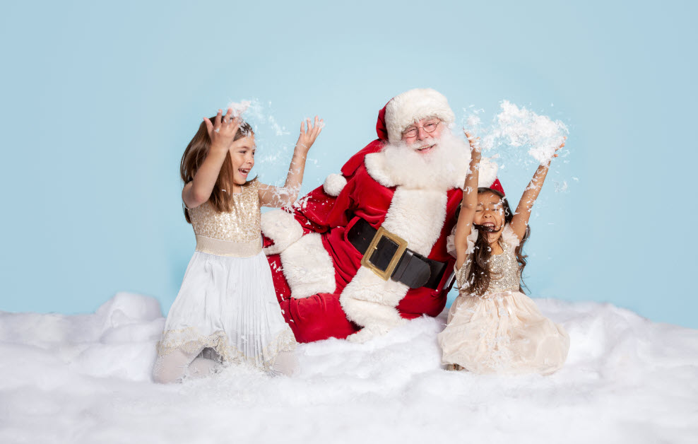 Santa and two young girls playing in snow