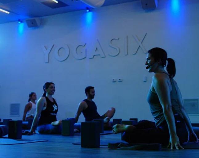 Instructor leading Yoga Six class on floor