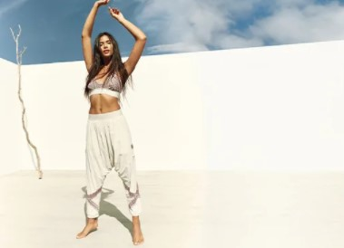 woman in joggers with her hands up