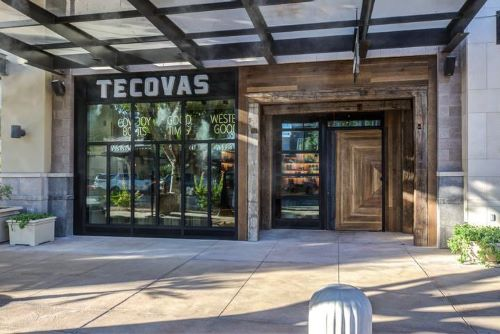 wooden store Front with white letters spelling out Tacovas.