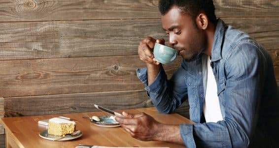 Man sitting drinking coffee texting