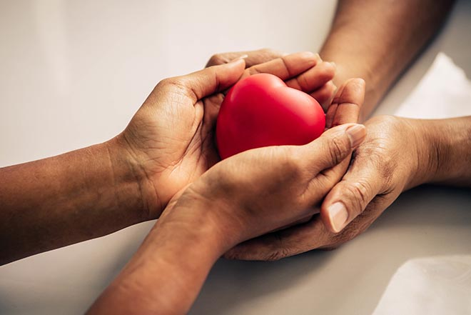 Two sets of hands holding a red heart