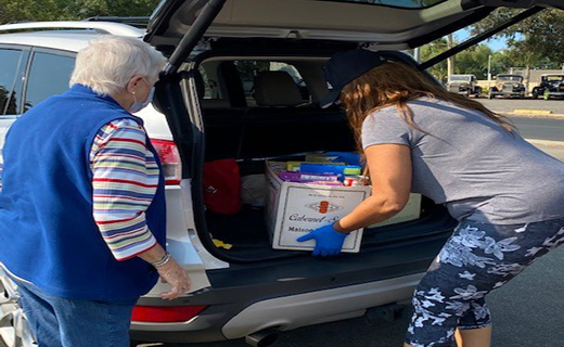 Volunteer getting boxes of donated food from a trunk