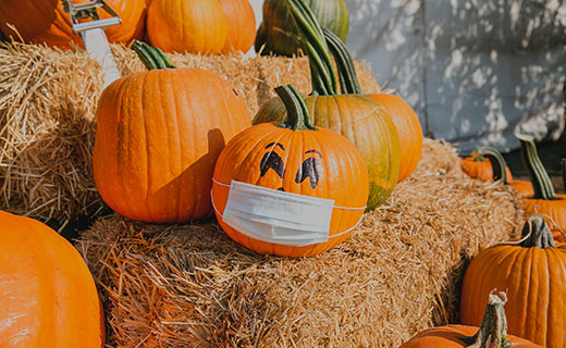 Pumpkins sitting on hay bales with one wearing a face mask