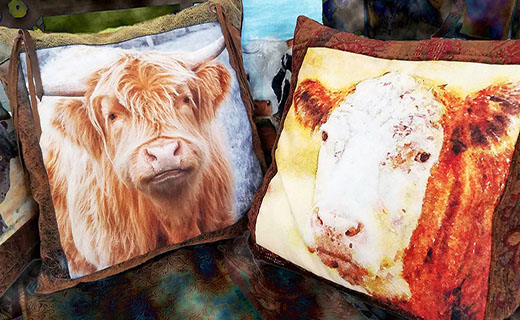 Two pillows each with a cow painted on them