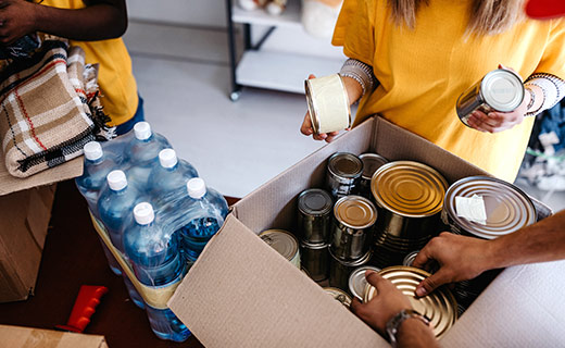 Multiple hands placing canned food in a cardboard box