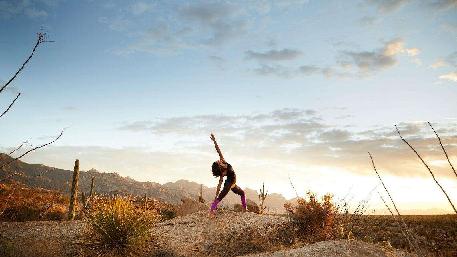 A woman doing a yoga pose, desert, cactus, mountains