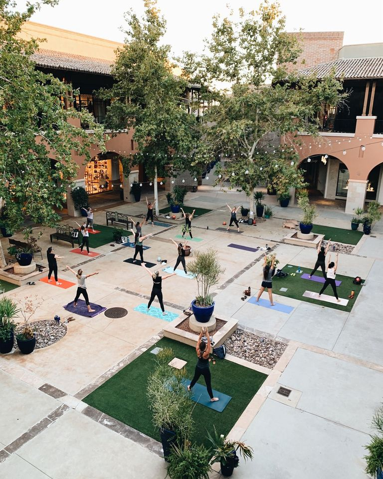 A group of women working out in an outdoor courtyard