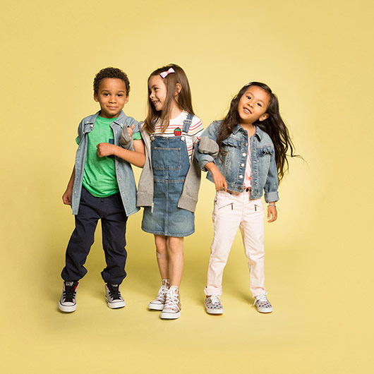 3 young children, linked arms and smiling