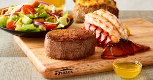Outback steak, lobster and salad on a cutting board