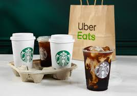 Starbucks coffees in a holder by an Uber Eats bag