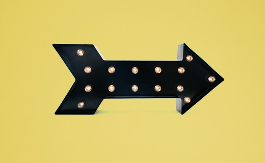 Illuminated arrow sign on a yellow background