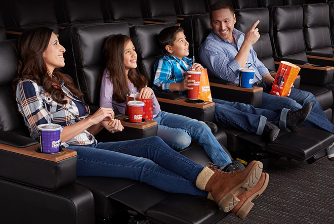 Family of four sitting with their legs extended in the harkins electronic reclining chairs with popcorn and soda.
