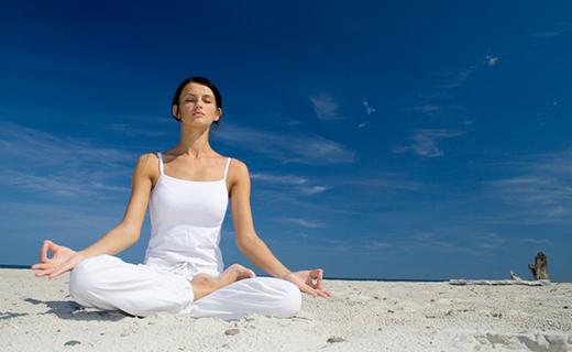Woman on beach doing yoga move