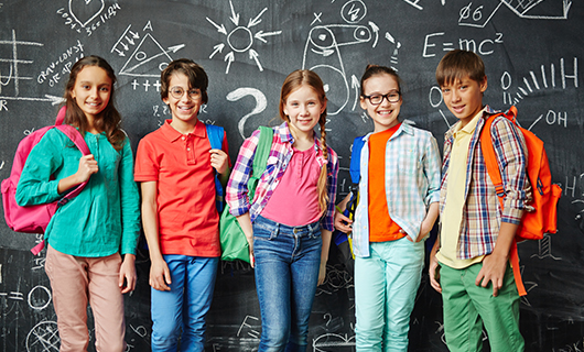 Five children in bright clothes standing in front of a blackboard