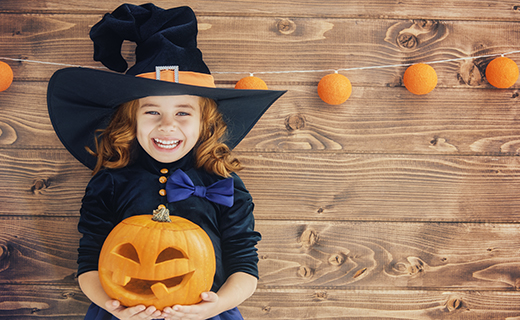 Young girl in a witch costume holding a carved pumpkin
