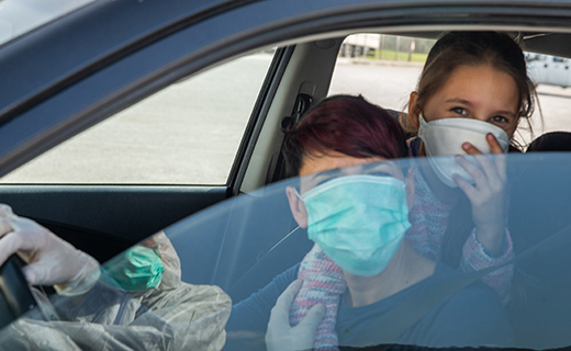 Two people wearing face masks and looking out a car window