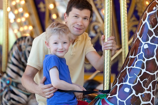 dad and son on merry go round