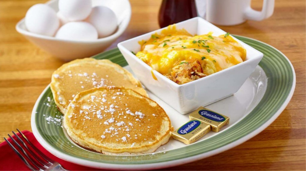Plate of pancakes with powdered sugar on them and a square bowl with cheesy eggs