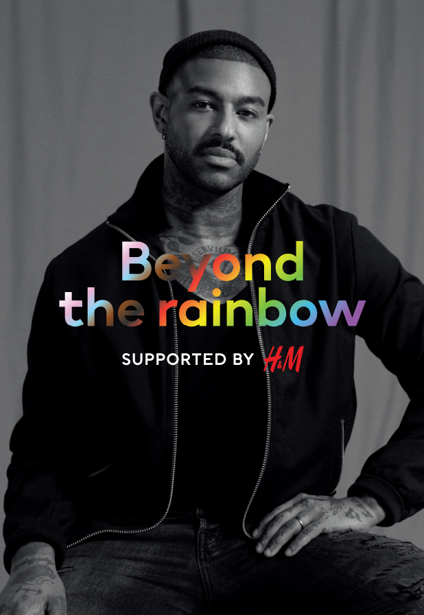 """Man with black zip up jacket and black beanie with a mustache and tattoos with """"Beyone the rainbow"""" in rainbow colors"""
