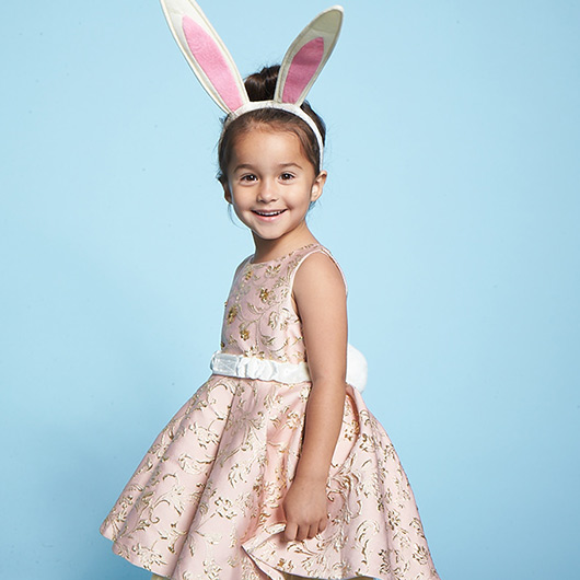 Little girl with wearing a pink dress and Bunny ears.