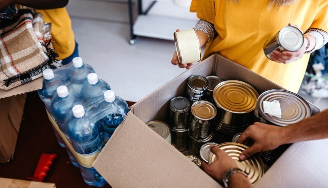 People putting canned food in a box.