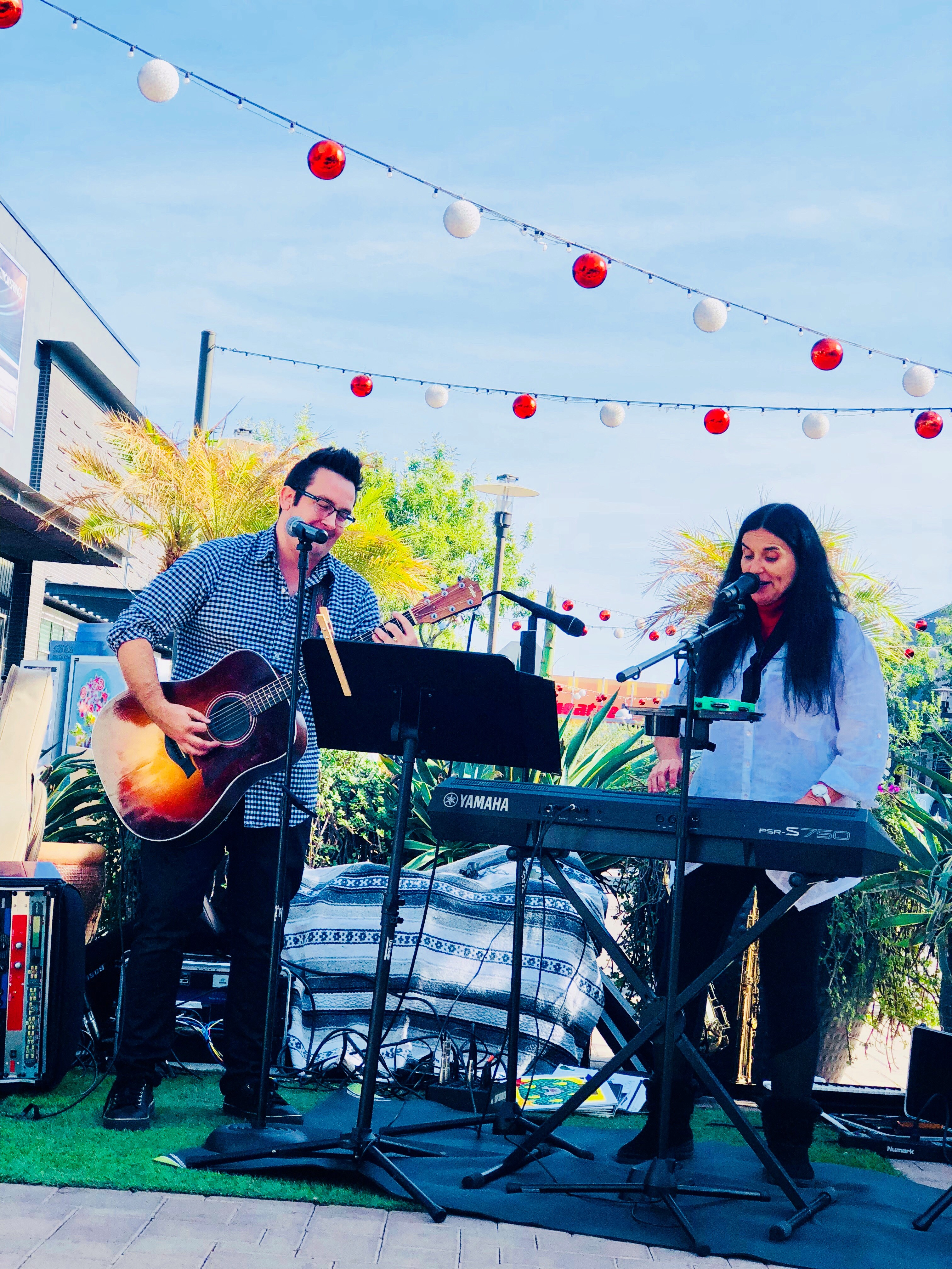 Guitarist and keyboard player singing holiday music.