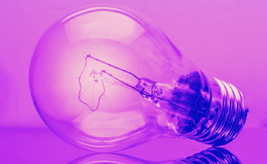 Purple lightbulb on a reflective surface with a purple background.