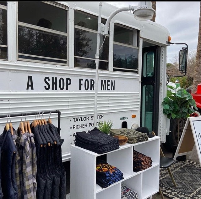 """White bus reading copy """"A Shop For Men"""" with merchandise set up in front of it."""