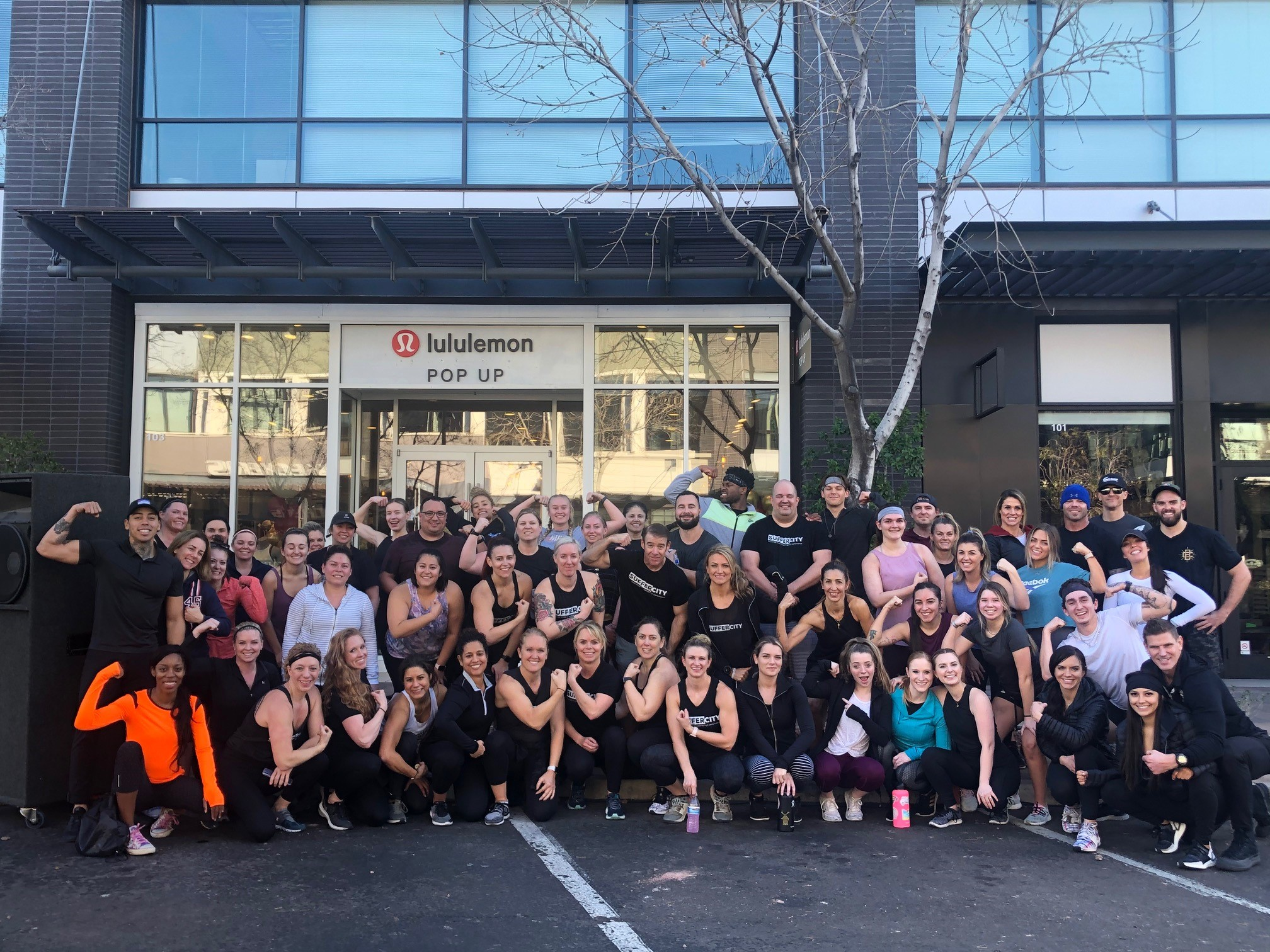 100 people in front of the lululemon store flexing their arm muscles