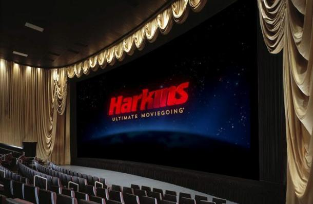 A big movie screen with Harkins displayed surrounded by curtains and theater seating.
