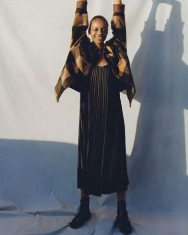 Girl raising both arms is wearing silk dress and lug boots