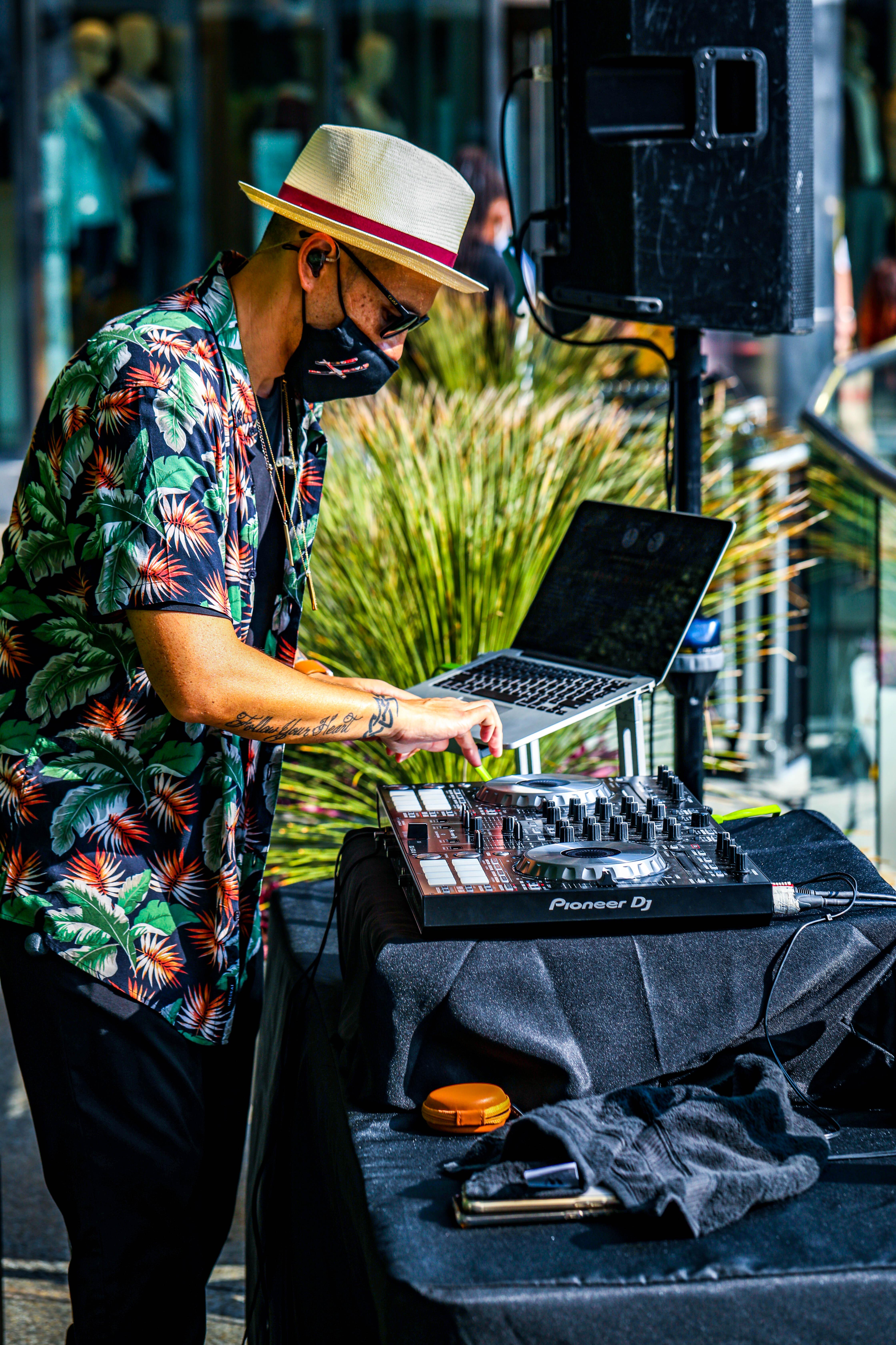 Tatooed DJ wearing hat, smiling at turntable