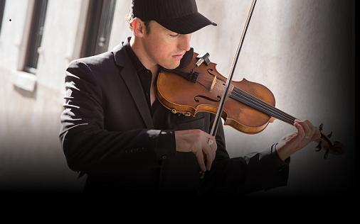 Musical performer Josh Vietti in dress suit and black baseball cap playing his violin.