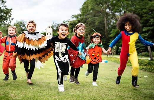 Children in halloween costumes running in a field smiling