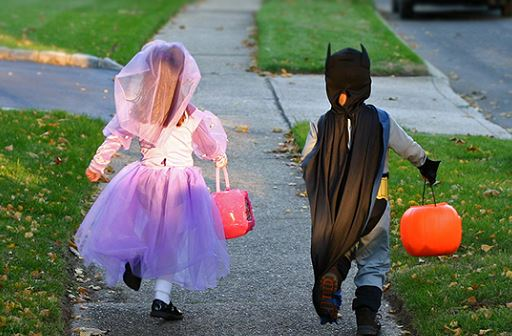 image from behind of 2 children walking down the sidewalk with their candy bags for Halloween trick or treating. Female child dressed in pink and purple princess dress with bright pink candy bag and male child in grey and blue batman costume with black cape and orange jack-o-lanter pumpkin for candy bag.