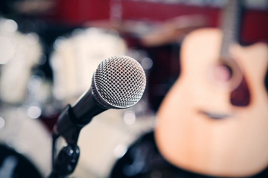 microphone in focus with  drum set and acoustic guitar in background