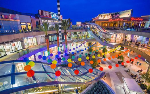 Center Plaza of the Santa Monica Place in the evening showing the Lanterns of Love, lit up, rainbow color (yellow, orange, red, purple, blue and green) rows of lanterns hanging across the rails of the 3rd level in celebration of Pride month in the city of Santa Monica.
